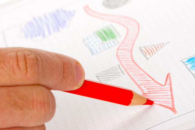 Businessman sketching success diagram by red pencil